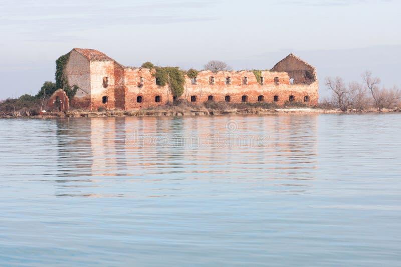 Edificio arruinado abandonado viejo de la isla de Madonna del Monte en la puesta del sol en la laguna de Venecia foto de archivo libre de regalías