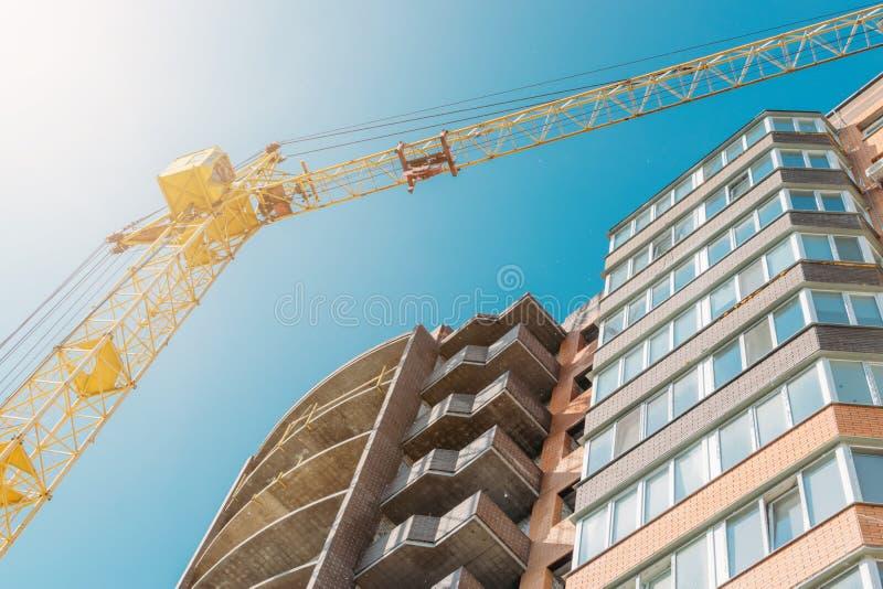 Edificio bajo construcción y grúa de construcción contra el cielo azul y el sol brillante el día de verano Visi?n inferior foto de archivo