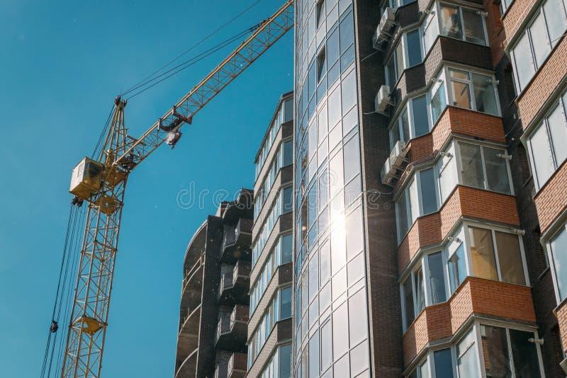 Edificio bajo construcción y grúa de construcción contra el cielo azul y el sol brillante el día de verano Visi?n inferior imagen de archivo libre de regalías