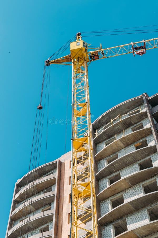 Edificio bajo construcción y grúa de construcción contra el cielo azul y el sol brillante el día de verano Visi?n inferior imagenes de archivo