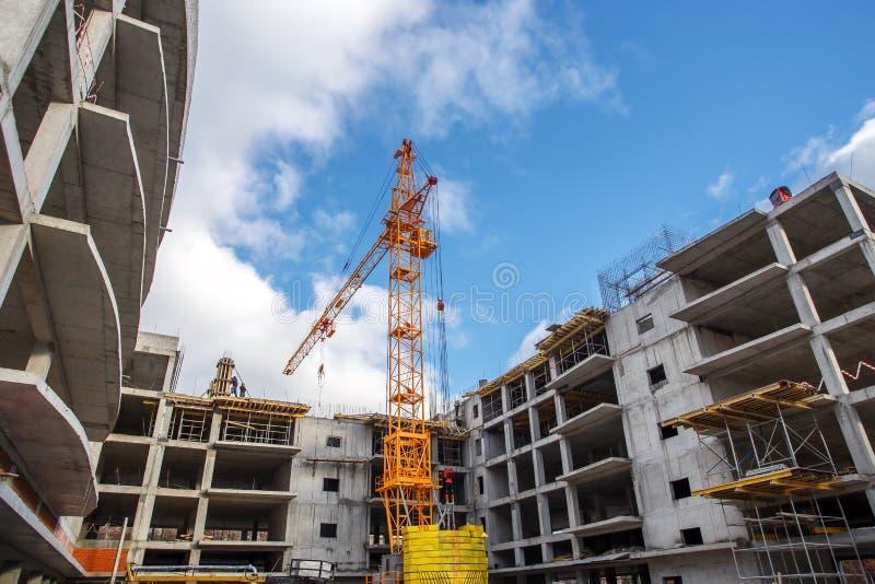 Edificio concreto de los ladrillos de la construcción de la grúa en ciudad fotos de archivo