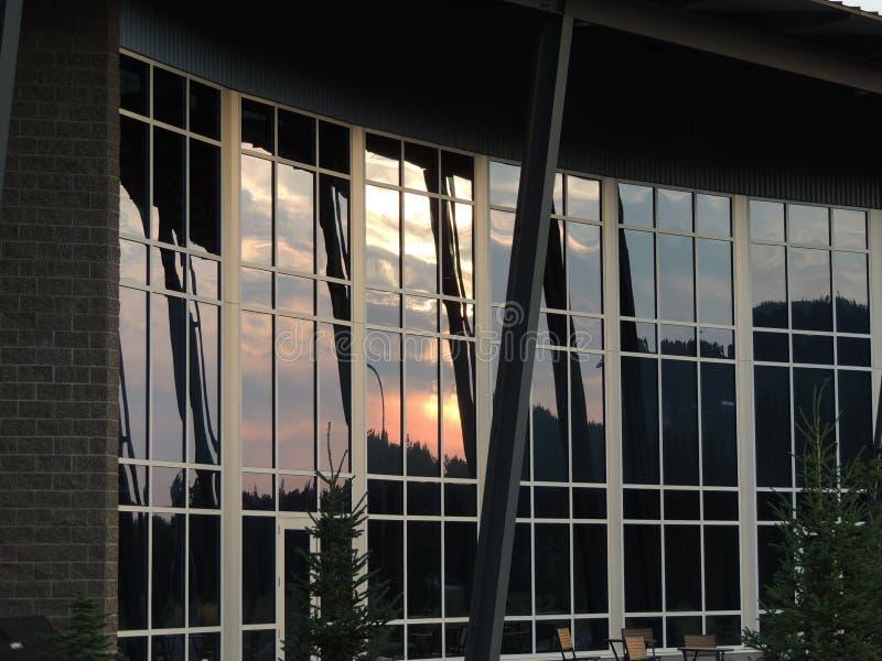 Edificio de conexión en cascada de la reflexión de la puesta del sol fotografía de archivo