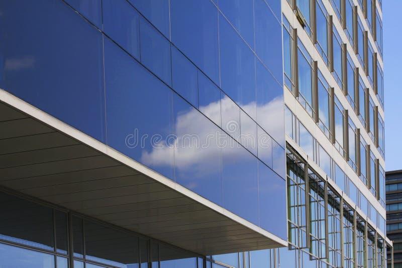 Edificio de highrise corporativo moderno con el cielo reflector de la fachada de cristal con las nubes imágenes de archivo libres de regalías