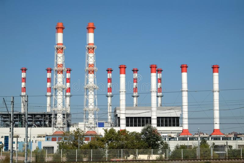 Edificio de la central eléctrica con muchos altos tubos industriales rojos y blancos sobre el cielo azul despejado claro en vista foto de archivo libre de regalías