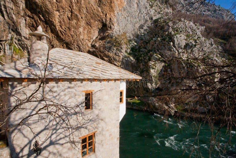 Edificio de ladrillo antiguo del monasterio histórico Blagaj Tekke de Sufi con un río y las montañas alrededor imagenes de archivo
