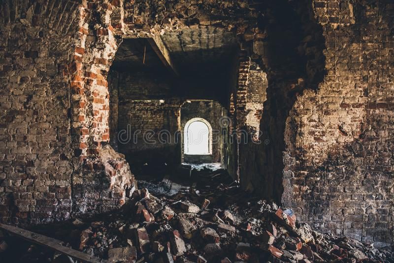 Edificio de ladrillo arruinado dentro, pared rota, opinión espeluznante oscura del pasillo imagen de archivo libre de regalías