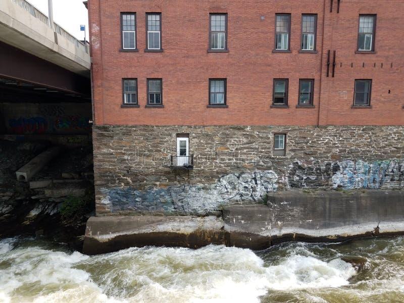 Edificio de ladrillos y rápidos en el río en Sherbrooke, Canadá fotos de archivo