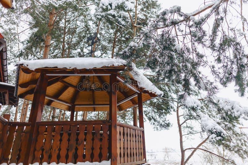 Edificio de madera debajo de árboles de pino nevados foto de archivo
