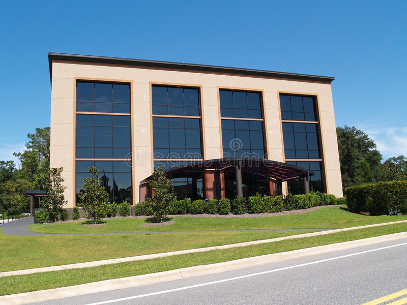 Edificio de oficinas de tres historias con el frente de cristal foto de archivo libre de regalías