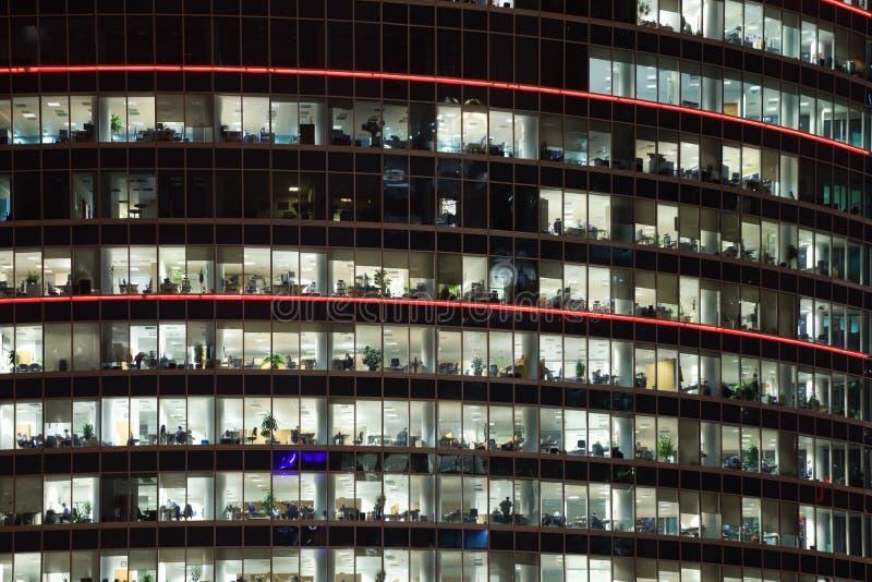 Edificio de oficinas moderno con las ventanas en la noche imagenes de archivo