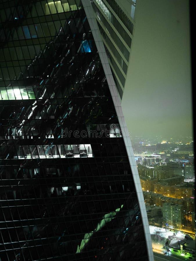 Edificio de oficinas de varios pisos en la noche, trabajando en horas extras de última hora en la oficina Edificio de oficinas mo foto de archivo libre de regalías
