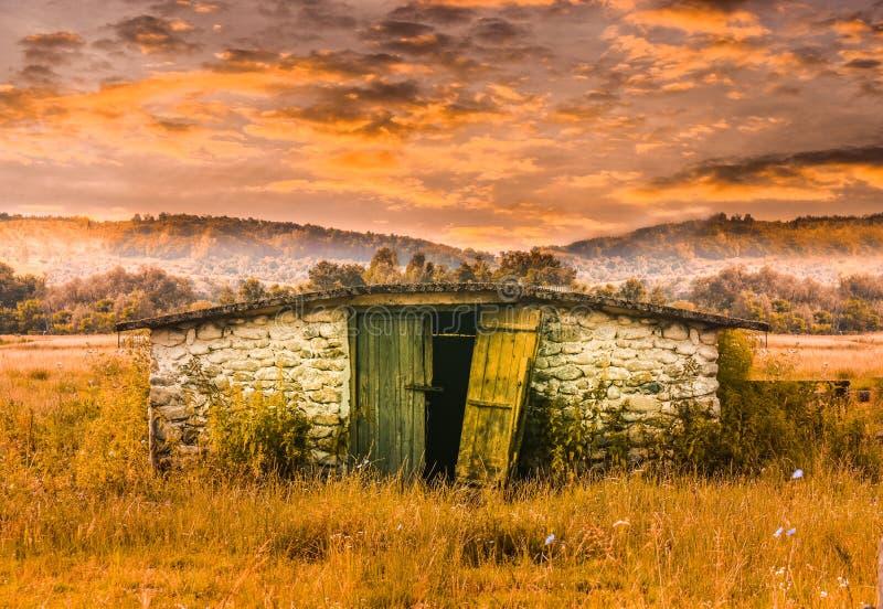 Edificio de piedra del granero en el campo de hierba en la puesta del sol Vertiente vieja abandonada en escena del cuento de hada imagen de archivo libre de regalías