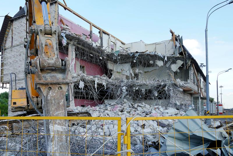 Edificio de varios pisos arruinado Un excavador demuele un edificio de varios pisos con una herramienta del cincel La técnica des imágenes de archivo libres de regalías