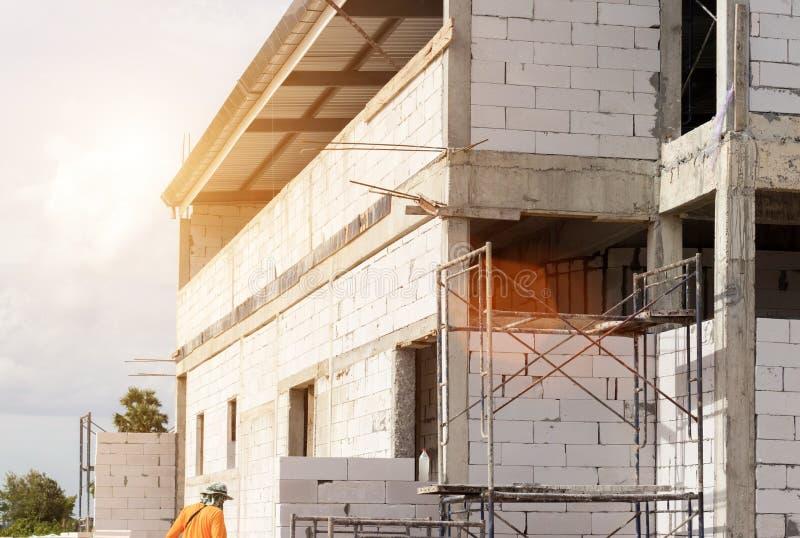 Edificio del emplazamiento de la obra con el andamio en nueva casa, arquitectura y alto concepto de la construcción de edificios foto de archivo