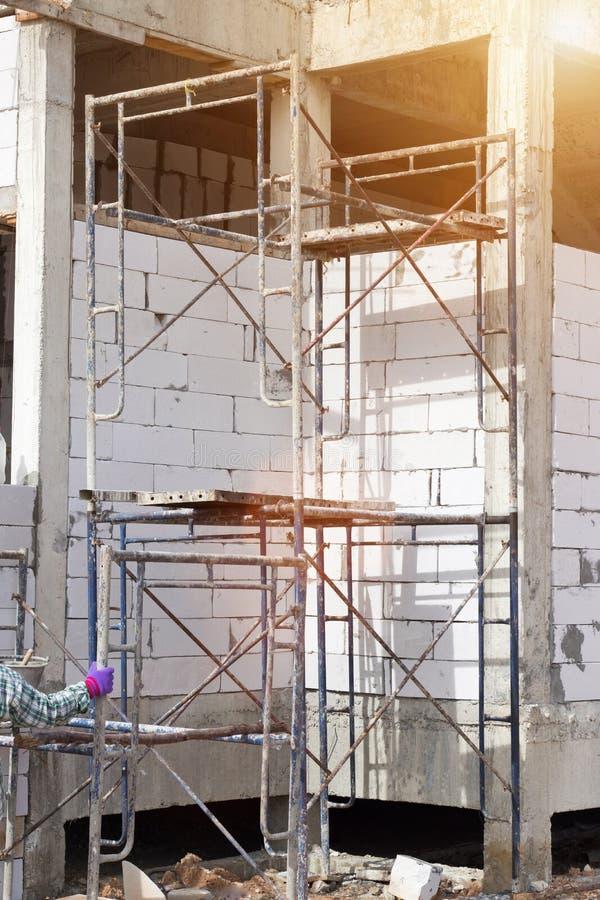 Edificio del emplazamiento de la obra con el andamio en nueva casa, arquitectura y alto concepto de la construcción de edificios fotografía de archivo