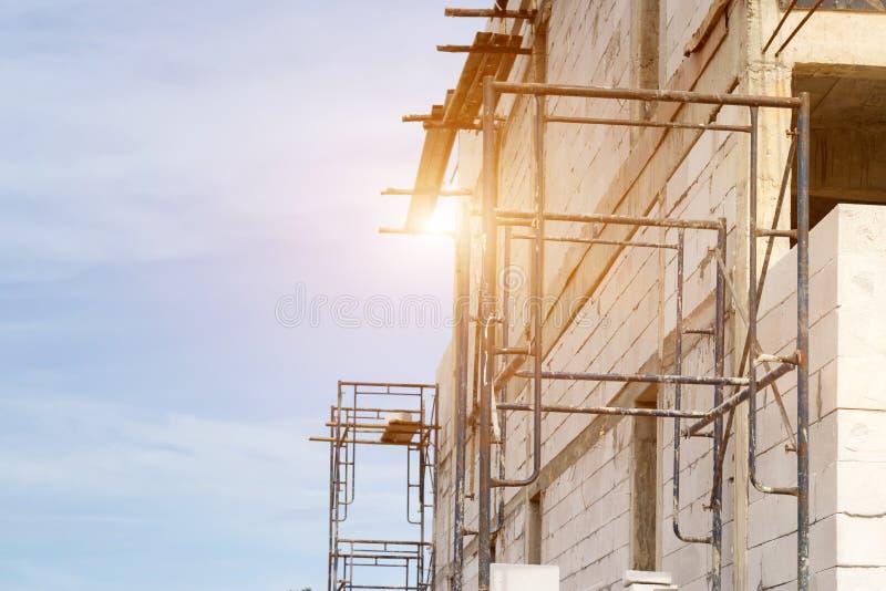 Edificio del emplazamiento de la obra con el andamio en nueva casa, arquitectura y alto concepto de la construcción de edificios fotos de archivo