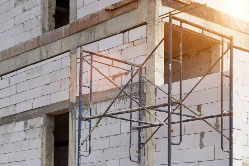 Edificio del emplazamiento de la obra con el andamio en nueva casa, arquitectura y alto concepto de la construcción de edificios imagen de archivo