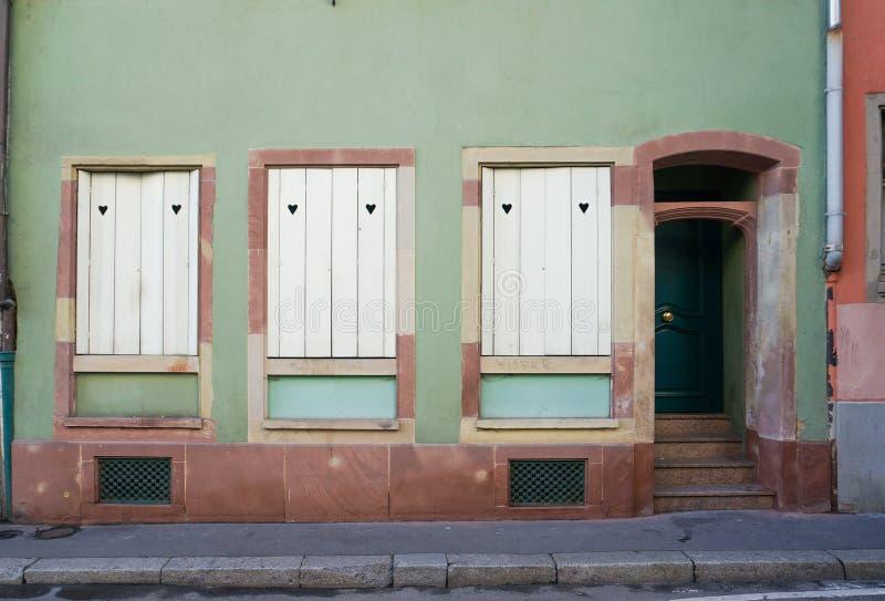 Edificio en colores pastel del marrón verde y oscuro con las ventanas y la puerta blancas imagenes de archivo