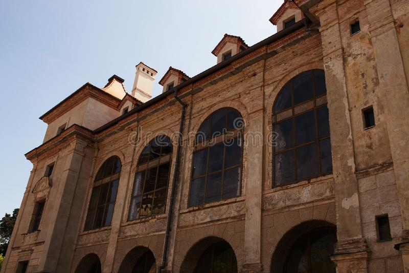 Edificio europeo viejo del palacio con los murales de la pared y las ventanas arqueadas grandes en fondo del cielo azul fotos de archivo