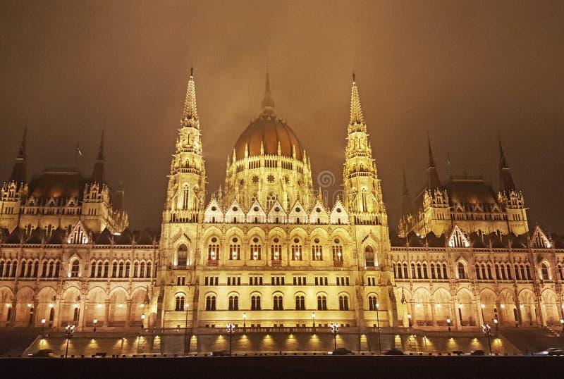 Edificio húngaro del parlamento de Budapest en la noche cerca del río Danubio imágenes de archivo libres de regalías