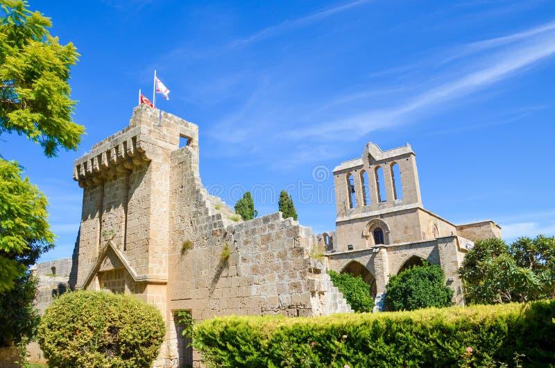 Edificio hermoso de la abadía medieval de Bellapais tomada con el parque adyacente y con el cielo azul Las ruinas del monasterio imagenes de archivo