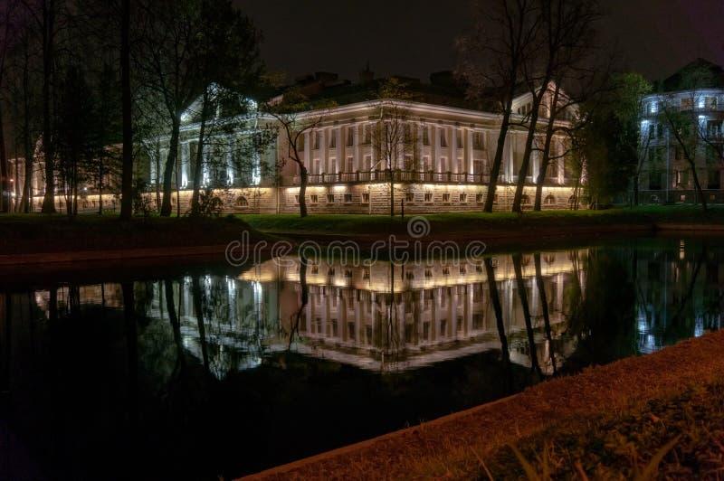 Edificio hermoso iluminado por las luces reflejadas en el río ilustración del vector
