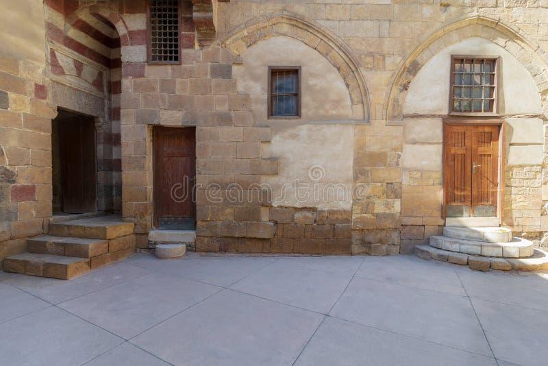 Edificio histórico de la era de Mamluk de la fachada con la pared de ladrillos de piedra del grunge y las puertas de madera del g fotos de archivo