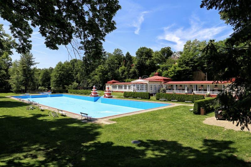 Edificio histórico del establecimiento de baño con la piscina azul imagenes de archivo
