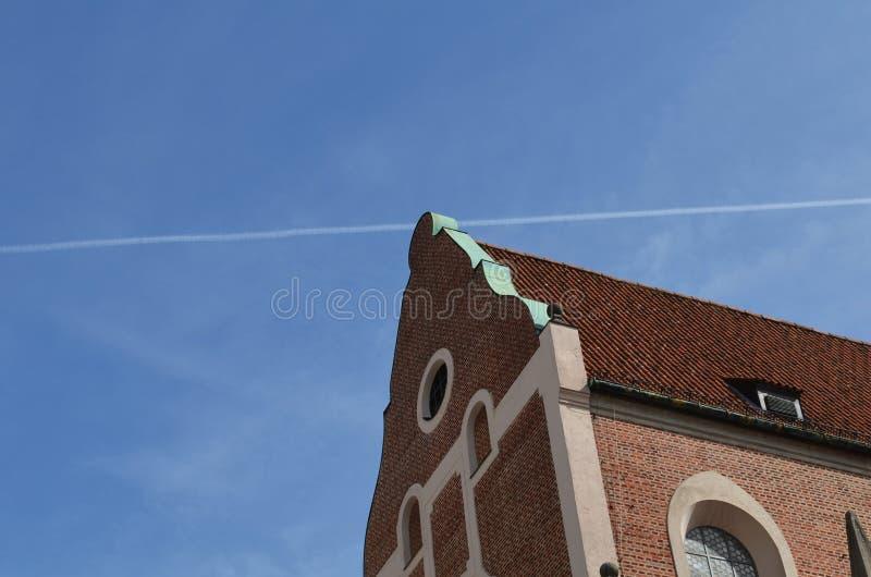 Edificio histórico hecho con los ladrillos rojos y un rastro de condensación de un avión en el cielo azul imagenes de archivo