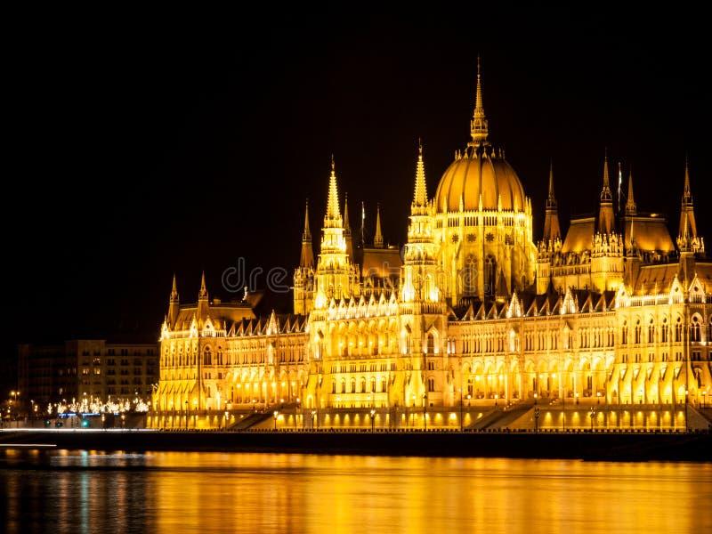 Edificio histórico iluminado del parlamento húngaro en el terraplén del río Danubio en Budapest por noche foto de archivo libre de regalías