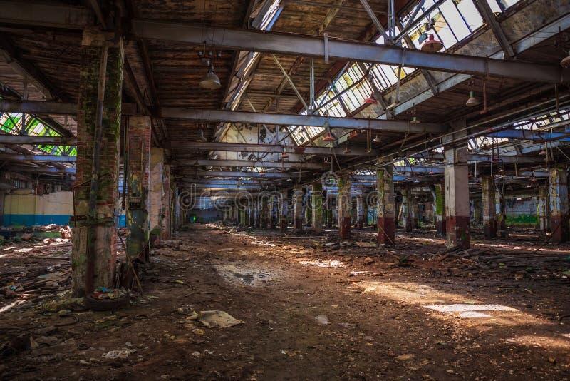 Edificio industrial arruinado abandonado del almacén o de la fábrica dentro, opinión del pasillo con perspectiva, ruinas y concep fotografía de archivo