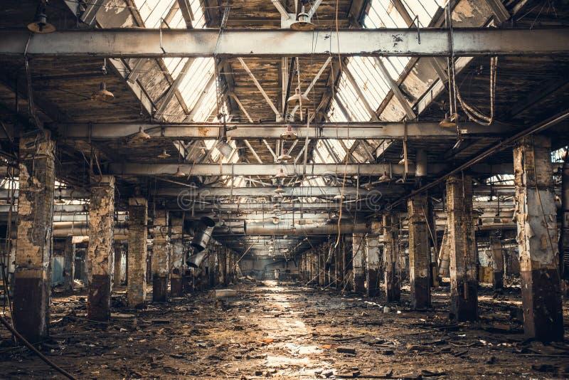 Edificio industrial arruinado abandonado del almacén o de la fábrica dentro, opinión del pasillo con perspectiva, ruinas y concep imagenes de archivo