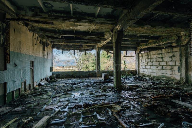 Edificio industrial putrefacto y overgrown abandonado en Sukhum, Abjasia Consecuencias de la guerra fotografía de archivo