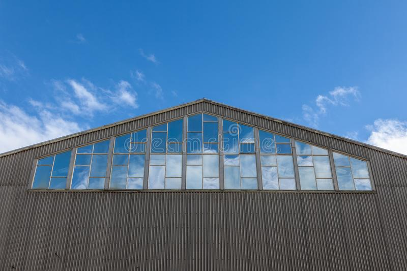 Edificio in magazzino con cielo azzurro riflesso in finestre, che scorre verso l'alto fotografia stock libera da diritti