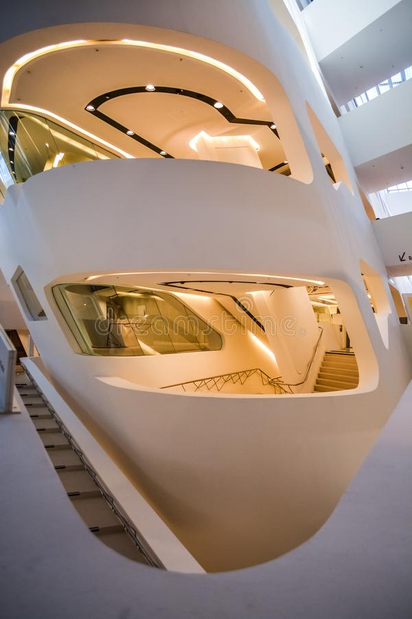 Edificio moderno adentro Con las paredes inclinadas y semicirculares, ventanas grandes y balcones, con la iluminaci?n Configuraci foto de archivo