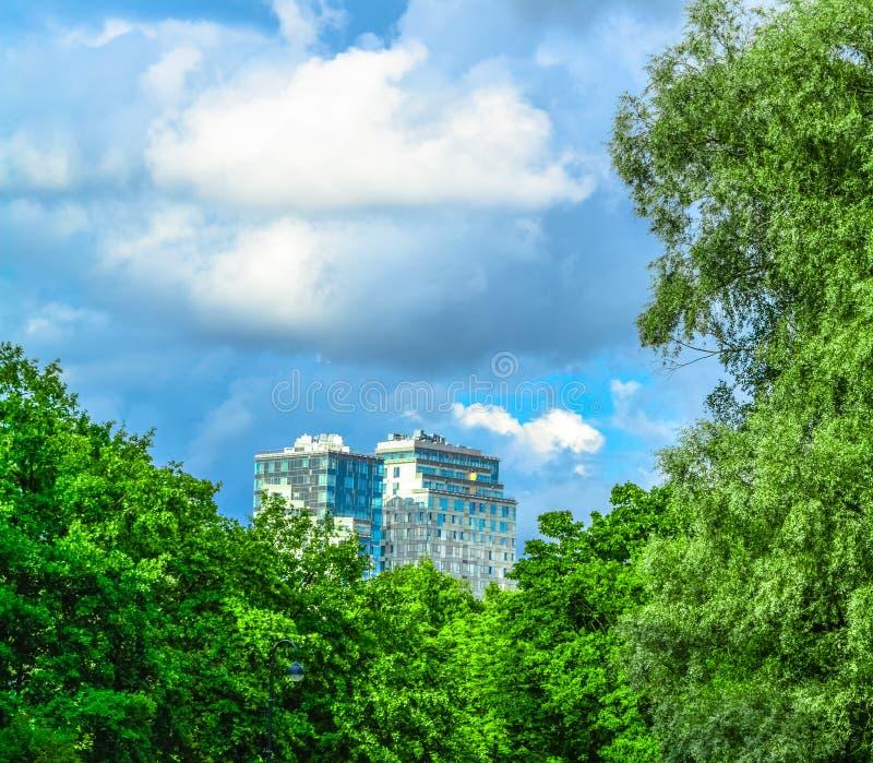 Edificio moderno de la ciudad entre árboles verdes y cielo azul con las nubes mullidas grandes imagen de archivo