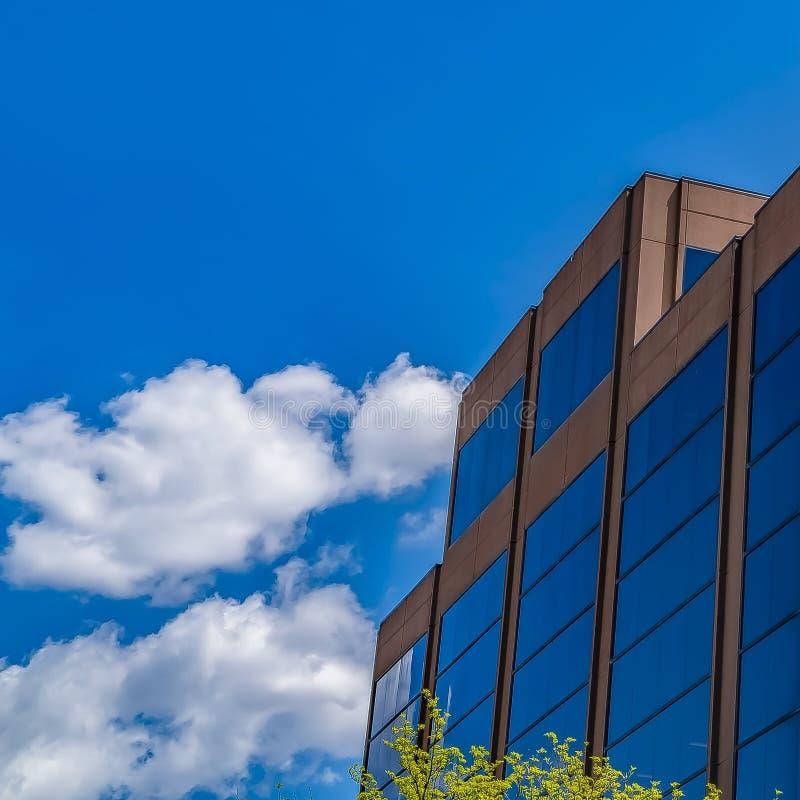 Edificio moderno del cuadrado del capítulo con la pared de cristal azul contra el cielo azul con las nubes mullidas fotos de archivo libres de regalías
