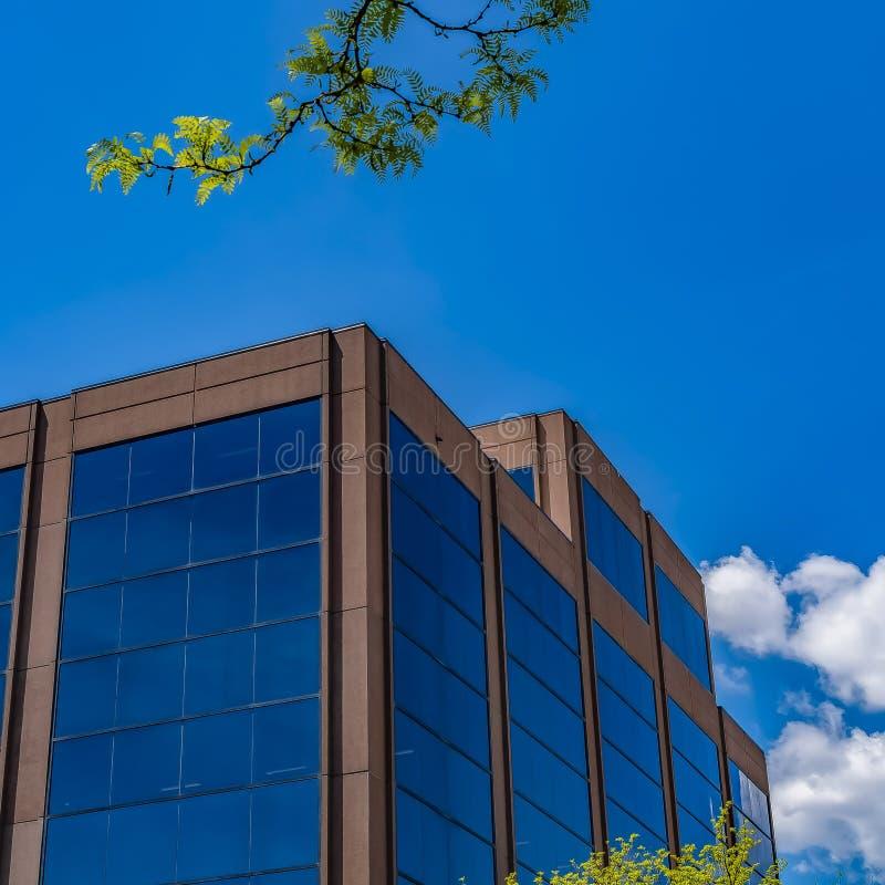 Edificio moderno del cuadrado con la pared de cristal azul contra el cielo azul con las nubes mullidas fotografía de archivo