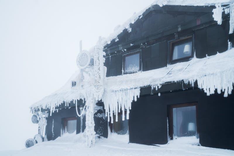 Edificio negro en las monta?as cubiertas con nieve e hielo, durante d?a muy fr?o en invierno fotografía de archivo