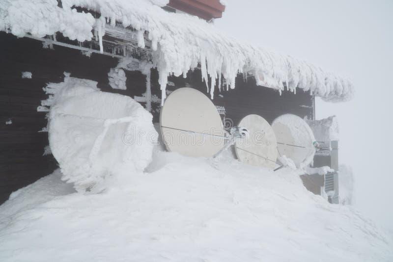 Edificio negro en las monta?as cubiertas con nieve e hielo, durante d?a muy fr?o en invierno imagen de archivo