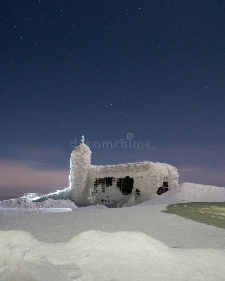 Edificio negro en las monta?as cubiertas con nieve e hielo, durante d?a muy fr?o en invierno imagenes de archivo