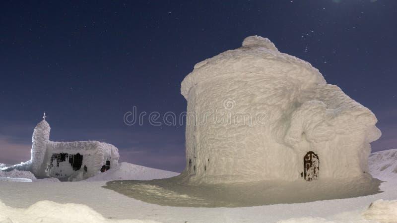 Edificio negro en las monta?as cubiertas con nieve e hielo, durante d?a muy fr?o en invierno imágenes de archivo libres de regalías
