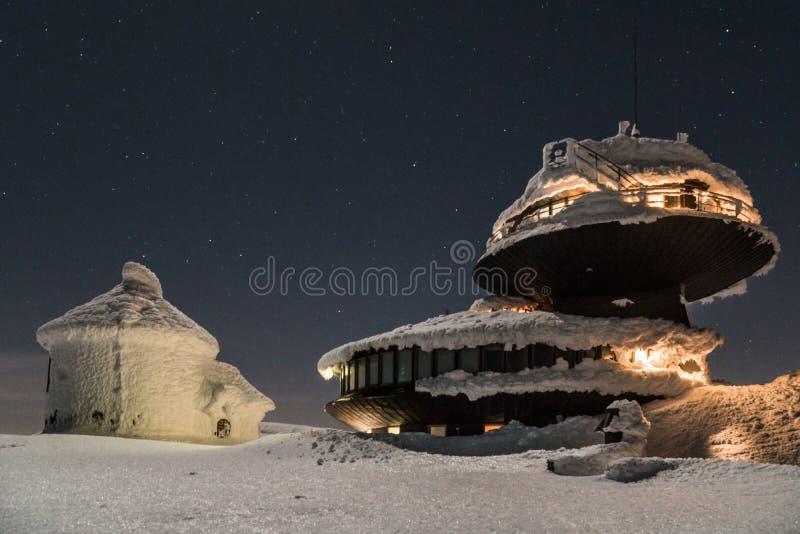 Edificio negro en las monta?as cubiertas con nieve e hielo, durante d?a muy fr?o en invierno foto de archivo libre de regalías