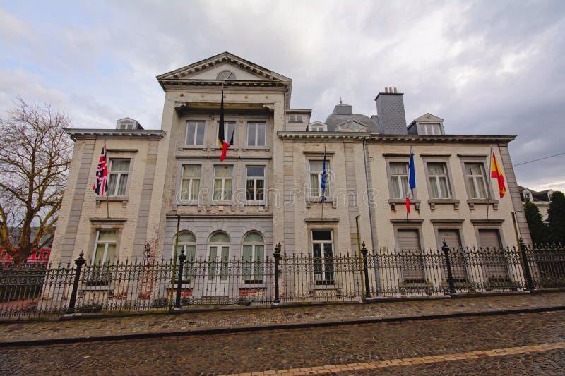 Edificio oficial neoclásico con las banderas de los países diferentes en Stavelot foto de archivo