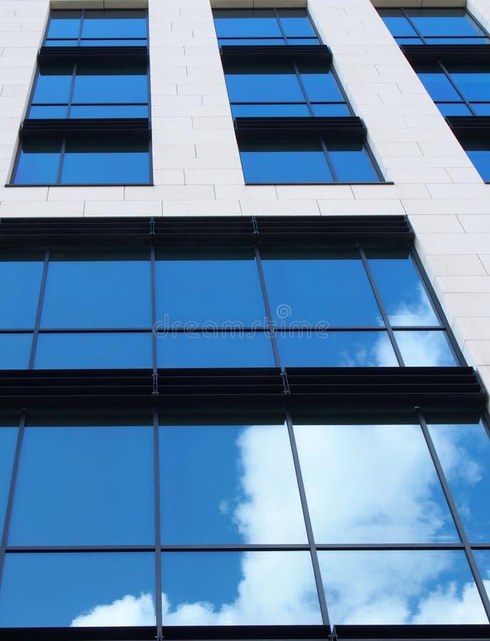 Edificio per uffici bianco moderno con le finestre di vetro rispecchiate che riflettono un cielo blu luminoso e le nuvole bianche immagine stock
