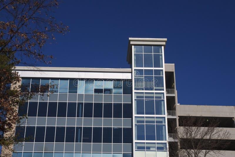 Edificio per uffici di vetro blu sotto il cielo blu profondo fotografie stock