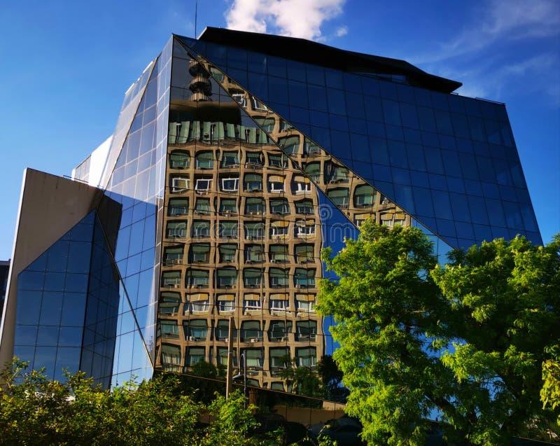 Edificio per uffici moderno ed il vecchio quartiere generale di TVR nello specchio immagine stock