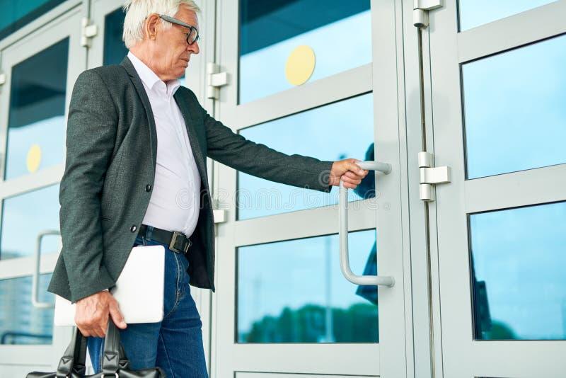 Edificio que entra del hombre de negocios mayor imagen de archivo
