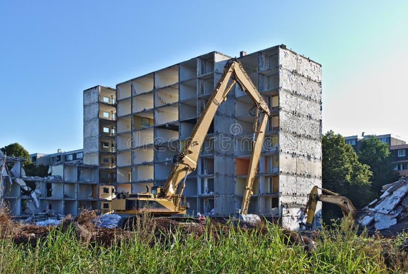 Edificio residencial demolido que es derribado por dos excavadores fotos de archivo