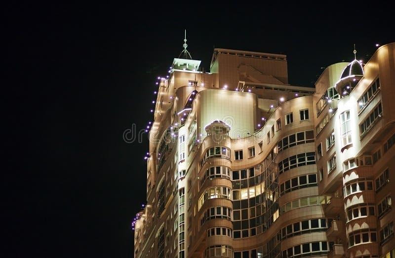Edificio residencial hermoso en la noche El edificio con la forma de la iluminación de la fortaleza y del diseñador foto de archivo